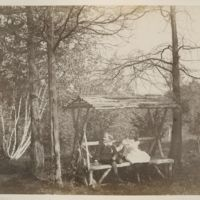 Boy and girl sitting on wooden-covered bench