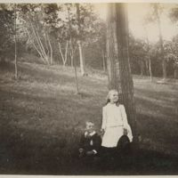 Boy and girl sitting and standing by a large tree