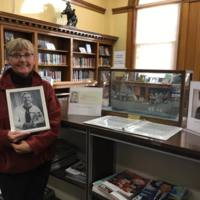 Daughter of Roy Olofson.  Mr. Olofson built the ship pictured.  It's a replica of the LST 310 that he served on in WWII.  It's been donated to the library's museum by the family.  She is holding a picture of her father.