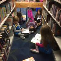 Some Daisy scouts catch up on their reading in the Children's Room while they wait for their meeting to begin.
